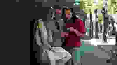 stock-footage-young-friends-with-smartphone-in-the-city-stabilized-shot