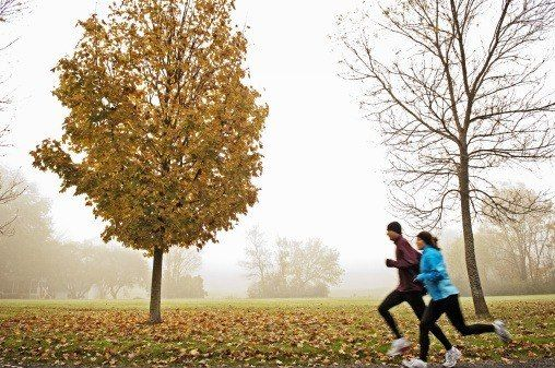 Couple running on foggy autumn morning